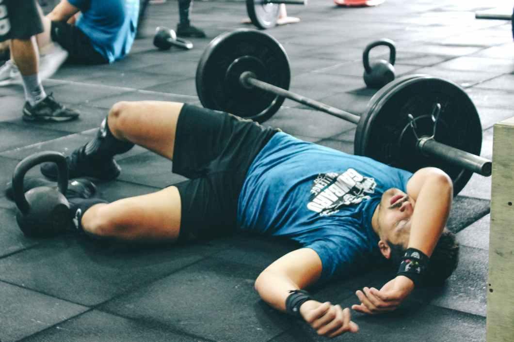 man lying on rubber mat near barbell inside the gym